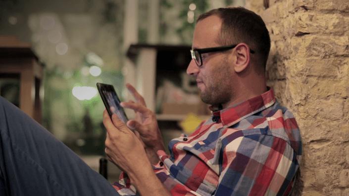 En man sittandes is soffan använder Learnifier kunskaps platform på en iPad